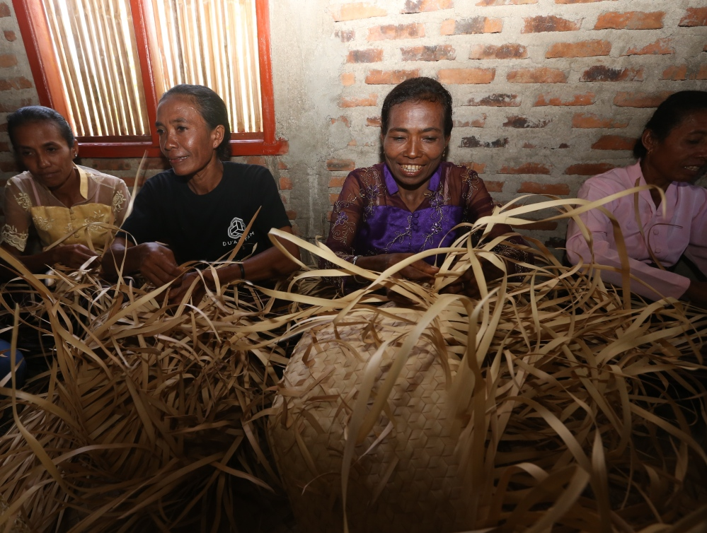 Mama Bernadete dan para mama lainnya sedang mengerjakan anyaman di Rumah Du'Anyam